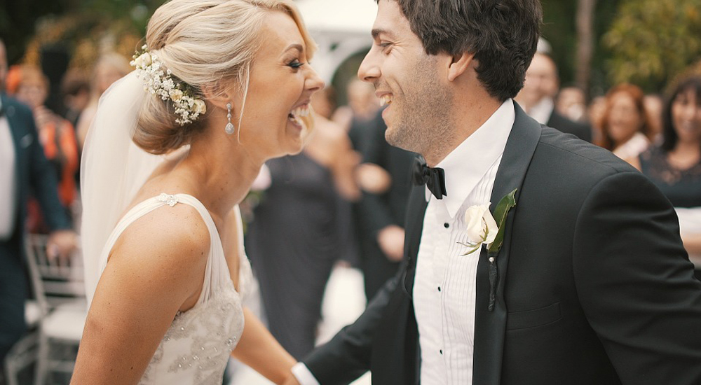 Couple on wedding day smiling at each other.