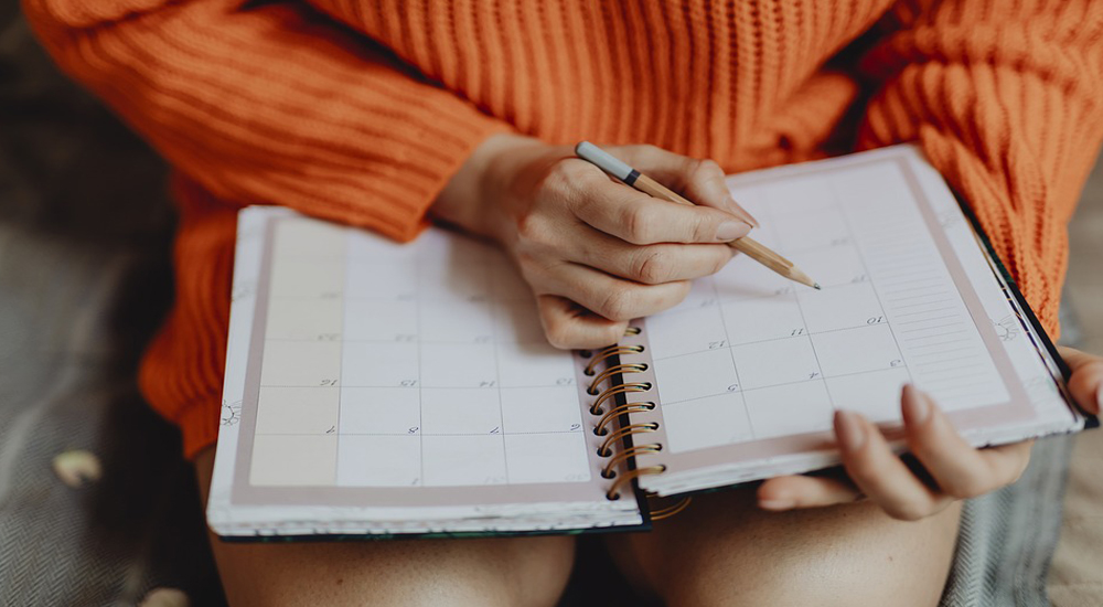 Woman wearing bright orange jumper with diary and pencil.