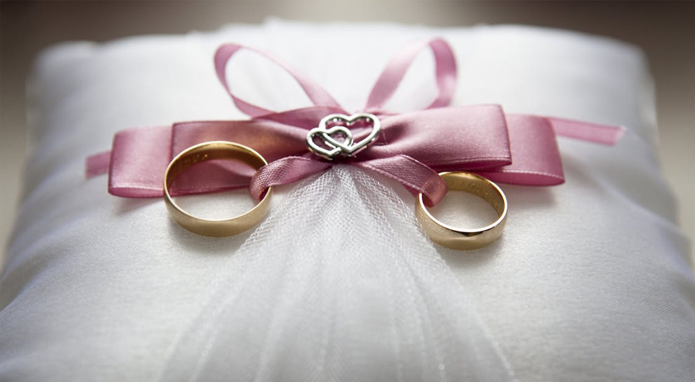 Two gold wedding rings attached to white cushion with pink ribbon.