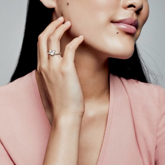 Model with long dark hair wearing pink top and Pandora Disney Mickey Silhouette ring