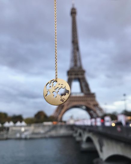byBiehl gold plated world pendant with Eiffel Tower in the background