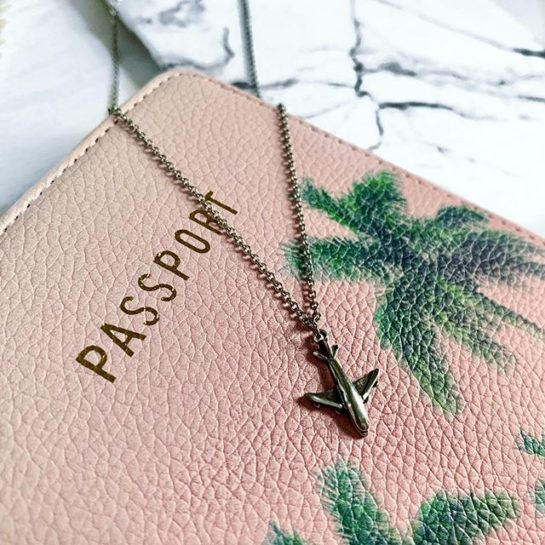 Sentiments aeroplane pendant draped over pink passport decorated with palm trees.