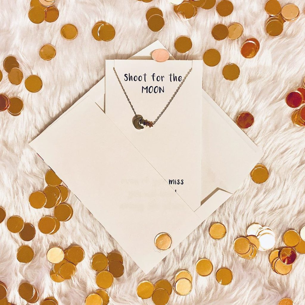 TJH Sentiments necklace in envelope surrounded by gold confetti