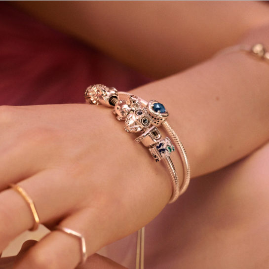 woman wearing two Pandora Moments charm bracelets
