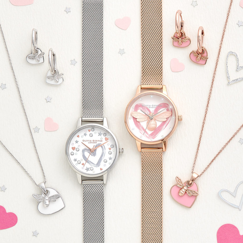 two watches, one rose gold and one silver, laid down with heart shaped jewellery from Olivia Burton