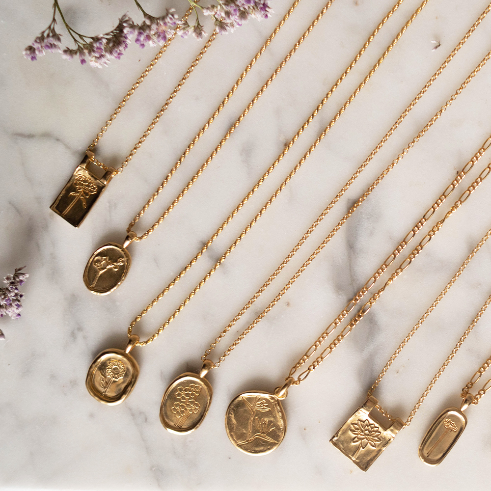 Daisy London Floriography necklaces laid out on a marble surface